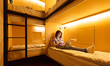 girl-in-hostel-on-bed-with-laptop