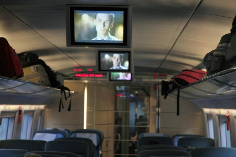 Luggage and tv screen in Le Frecce train