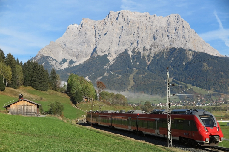 Photo d'un train rouge traversant une vallée entourée d'immenses falaises grises