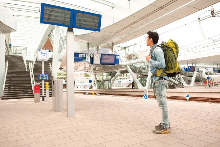 Image of a backpacker checking train times screens on a railway platform