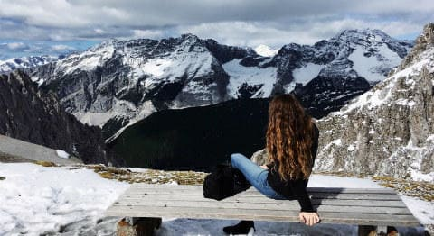 winter_travel_inspiration_-_girl_looking_over_the_spectacular_view_from_the_top_of_nordkette_mountain_in_innsbruck_austria_2